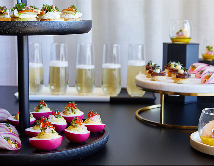 champagne glasses and other hors d'oeuvres set on a table for a catering event