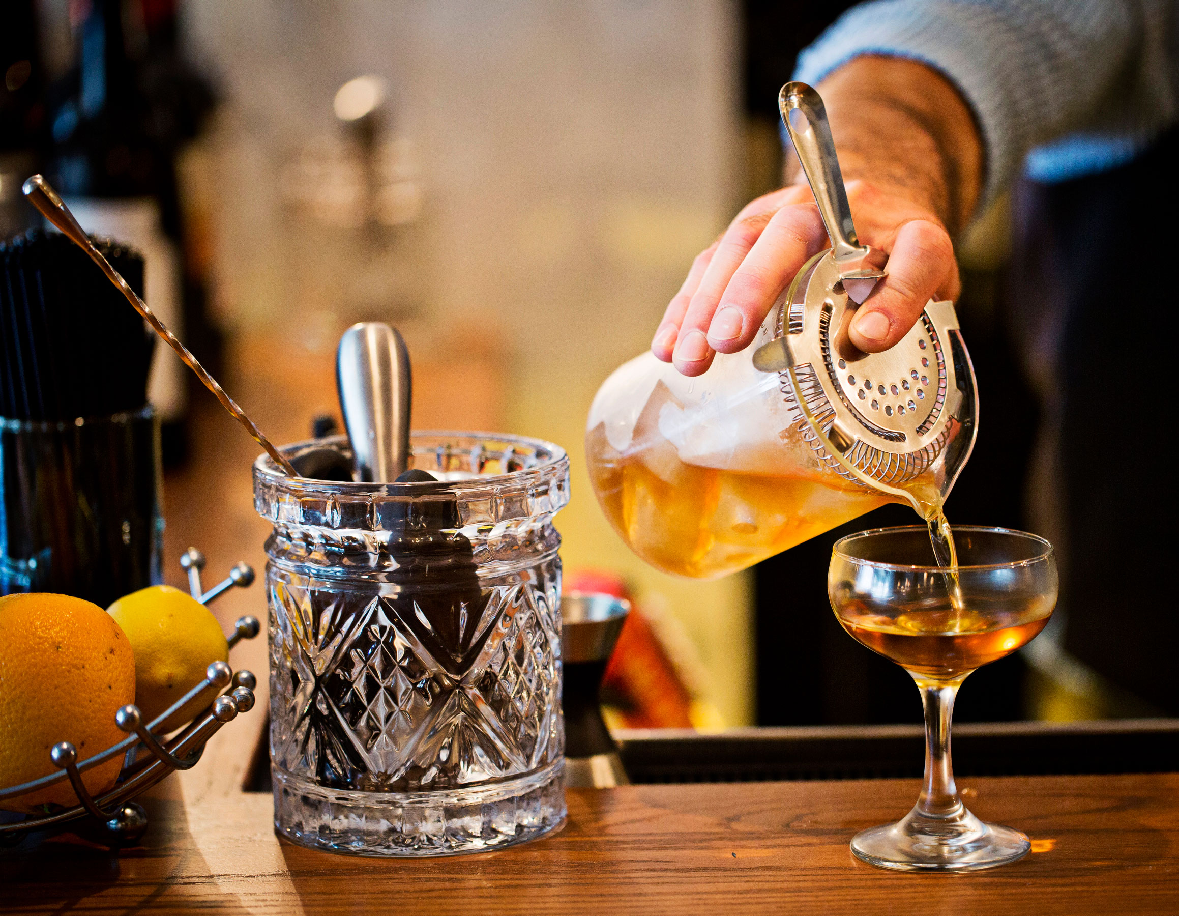 bartender pouring a craft cocktail into a glass