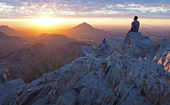 Man sitting at the top of a mountain peak overlooking the sunset