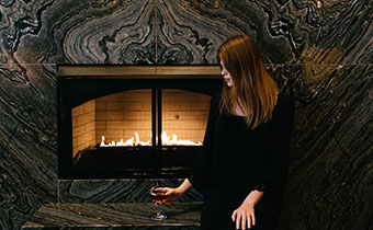 Woman holding a glass of wine in front of a fireplace