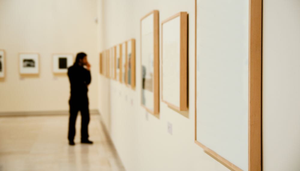 stark white art gallery lined with wood framed art hung in a straight line down a wall with a spectator in the distance